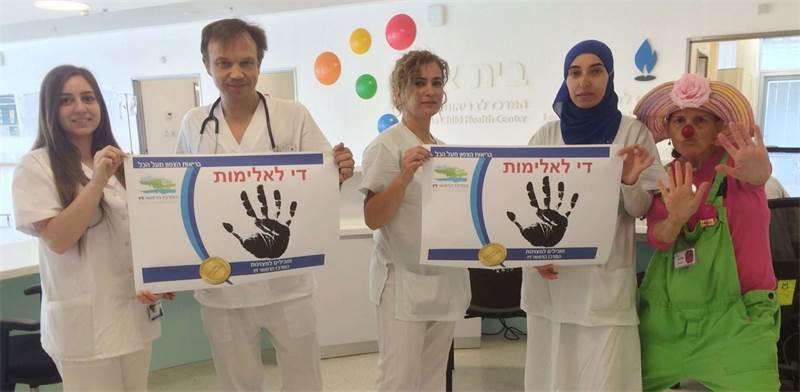 האחים והאחיות וליצנית רפואית במרכז הרפואי זיו בצפת, נושאים שלטים נגד אלימות / צילום: המרכז הרפואי זי