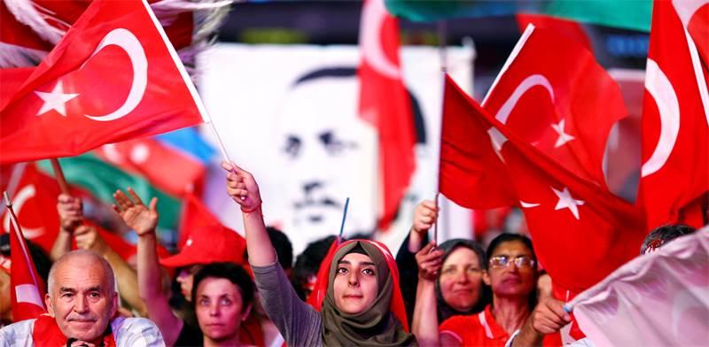 תומכי ארדואן אוחזים בדגלים ובכרזות עם דיוקנו / רויטרס