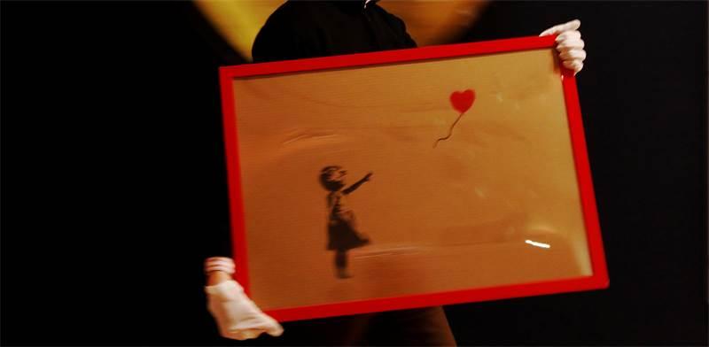 """ציורו של בנקסי """"ילדה עם בלון אדום"""" / רויטרס"""