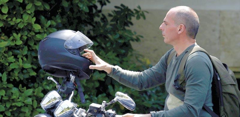 """יאניס ורופאקיס והאופנוע, ב־2015. המוטו הוא: """"סירוב קונסטרוקטיבי"""" /צילום: רויטרס, Kostas Tsironis"""