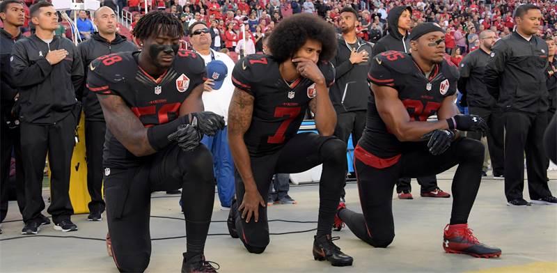 שחקני הפוטבול קולין קפרניק (במרכז), אלי הרולד ואריק ריד כורעים ברך בהשמעת ההמנון האמריקאי / צילום: רויטרס