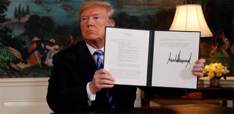 טראמפ מציג את חתימתו על הצו הנשיאותי לביטול הסכם הגרעין / צילום: ג'ונטן ארנסט, רויטרס