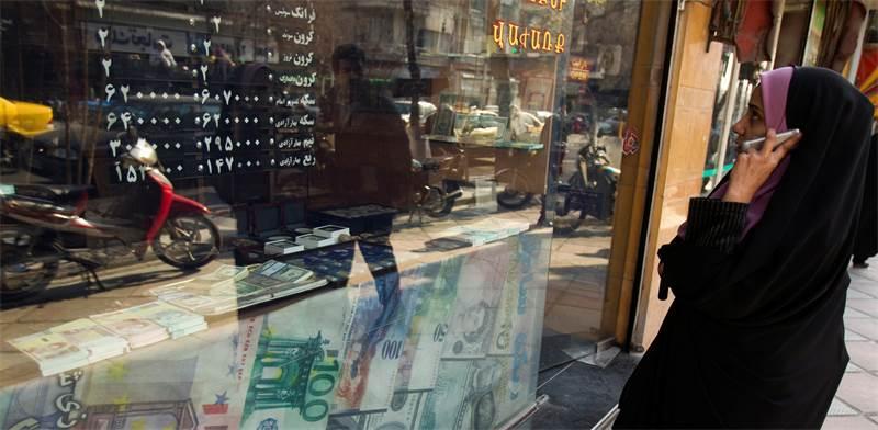 """תושבת טהראן בודקת שער מט""""ח אצל חלפן מקומי / צילום: רויטרס"""