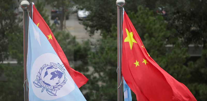 דגלי סין והאינטרפול / צילום:רויטרס Jason Lee
