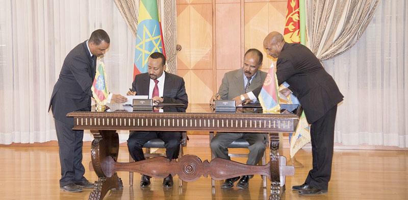 אבי אחמד ואייזייאס אפוורקי חותמים על הסכם השלום ./ צילום: רשת חברתית, רויטרס