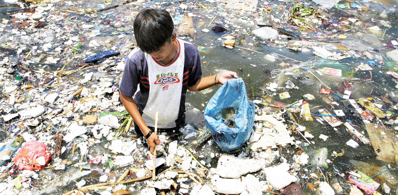 ילד מחפש פלסטיק למחזור במנילה / צילום: רויטרס