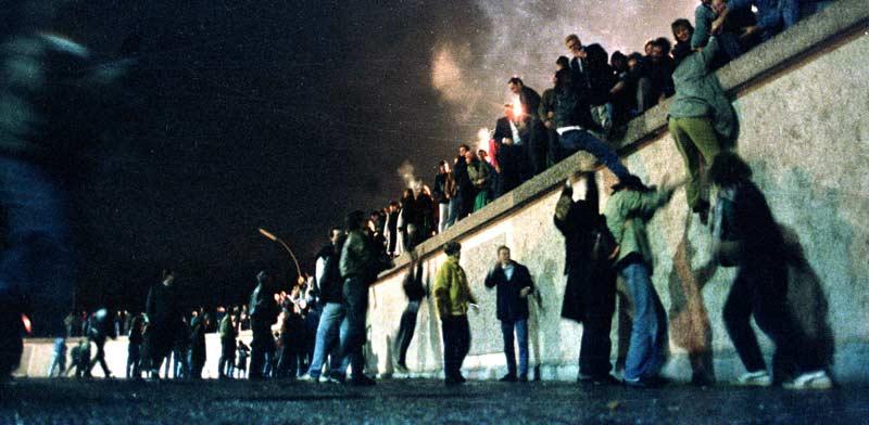 תושבי מזרח גרמניה מטפסים על החומה עם פתיחת הגבול בין שתי הגרמניות/ צילום:: רויטרס