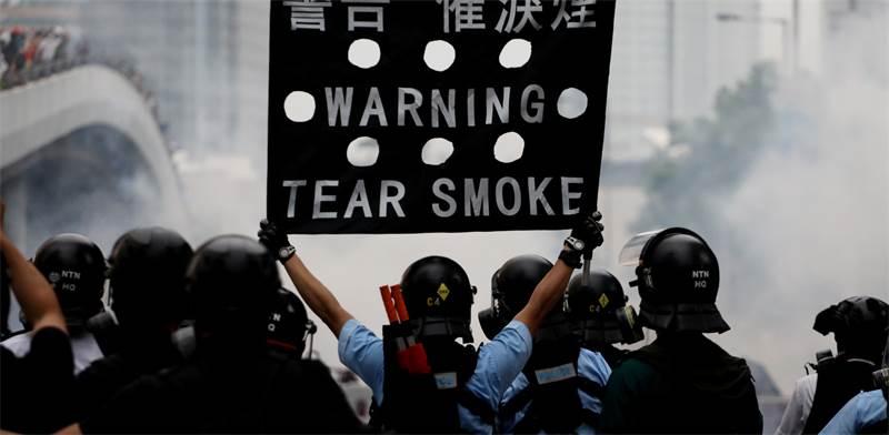 שוטר מזהיר מפגינים בעימותים בהונג-קונג / צילום: Athit Perawongmetha, רויטרס