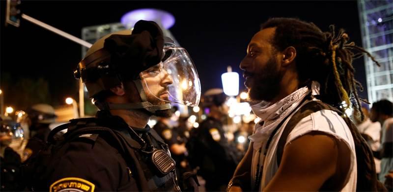 מפגין ושוטר במחאה על אלימות משטרתית / צילום: Corinna Kern, רויטרס