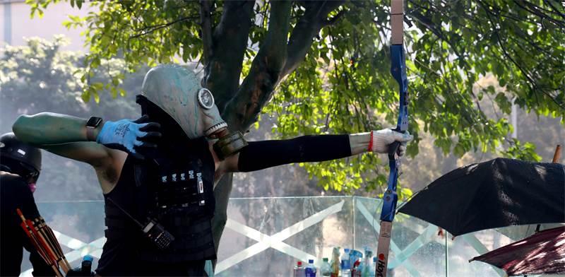 מפגין יורה בחץ וקשת במחאה בהונג קונג / צילום: Athit Perawongmetha, רויטרס