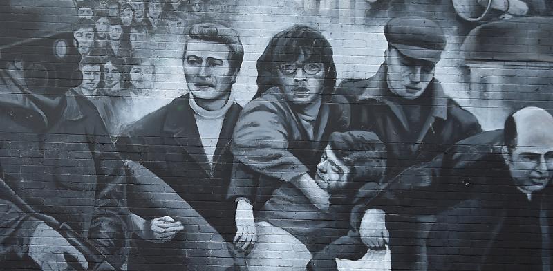 """תיירים צופים בציור קיר של אירועי """"בלאדי סאנדיי"""". הגבולות בין צפון אירלנד ואירלנד שוב במוקד המחלוקת / צילום: Clodagh Kilcoyne, רויטרס"""