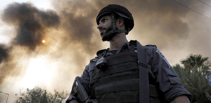חייל שומר בזמן שכוחות כיבוי האש מנסים לכבות את השריפה במפעל צעצועים בשדרות, שרקטה פגעה בו / צילום: רויטרס