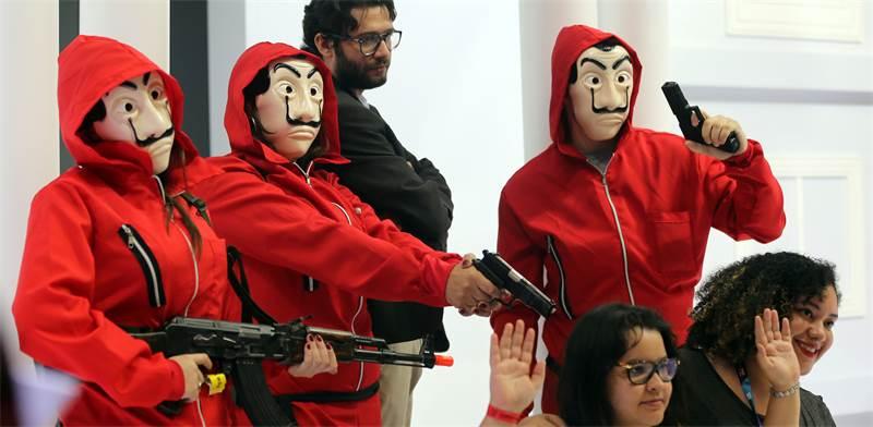 """אנשים מחופשים לדמויות מ""""בית הנייר"""" / צילום: Paulo Whitaker, רויטרס"""