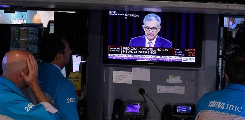"""סוחרים צופים בנאומו של יו""""ר הפד ג'רום פאואל לאחר החלטת הריבית / צילום: Brendan McDermid, רויטרס"""