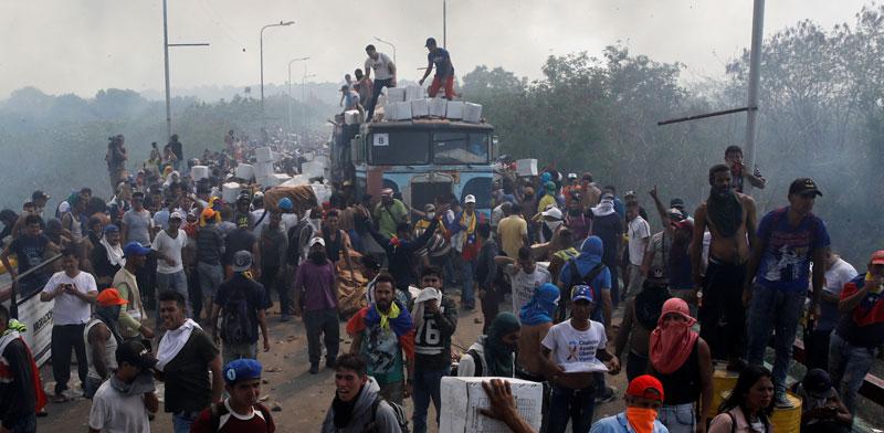 אנשי אופוזיציה פורקים משאית עם סיוע הומניטרי.  / צילום: רויטרס Marco Bello