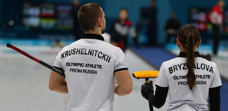 """צמד שחקני קרלינג רוסיים עם חולצות """"אתלטים אולימפיים מרוסיה"""" באולימפיאדת החורף ב־2018 /צילום:  Shutterstock"""