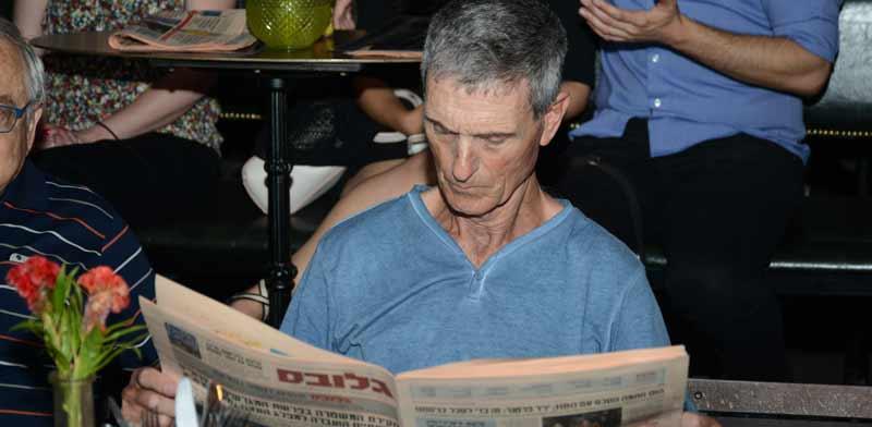 קורא בעיתון גלובס / צילום: איל יצהר