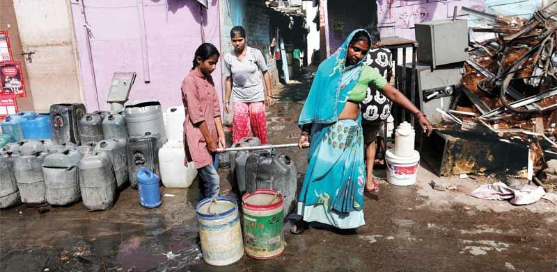 תושבים בהודו סוחבים מכלי מים שמילאו ממכלית ממשלתית / צילום: רויטרס, Adnan Abidi