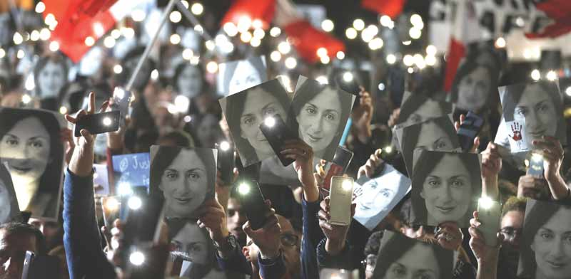 """מפגינים מחוץ למשרד רה""""מ מחזיקים בתמונה של העיתונאית דפני קארואנה-גליציה שנרצחה/ צילום: רויטרס, YARA NARDI"""
