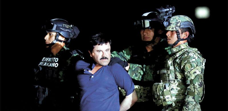 """חואקין גוסמן, אל צ'אפו, מלווה ע""""י שוטרים במקסיקו, 2016 /  צילום: רויטרס, Tomas Bravo"""