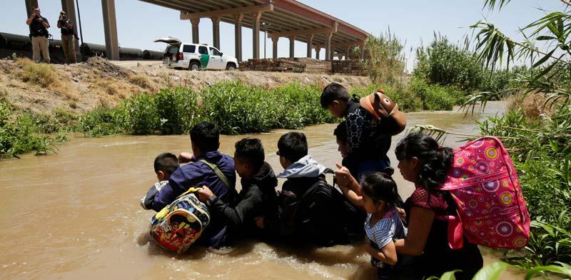 """מהגרים לא חוקיים מגואטמלה חוצים את נהר הריו בראבו שמפריד בין מקסיקו לארה""""ב / צילום: רויטרס, Jose Luis Gonzalez"""
