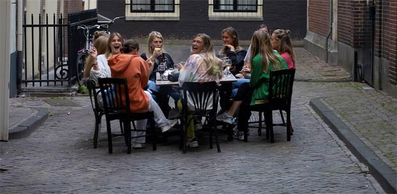 צעירות הולנדיות נפגשות באמצע רחוב ריק במהלך המגפה והסגר / צילום: Peter Dejong, Associated Press