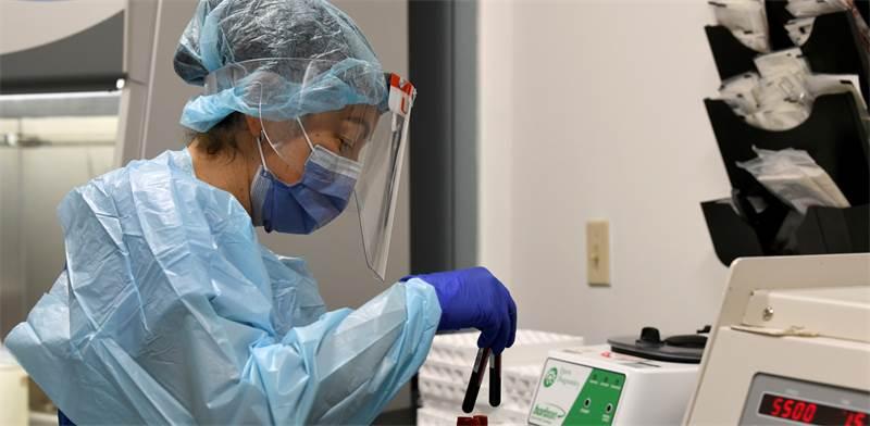 חוקרת בודקת מבחנות דם כחלק מהניסוי בחיסון של מודרנה לנגיף הקורונה / צילום: Taimy Alvarez, AP