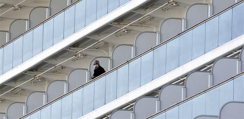 """נוסע בספינת """"דיימונד פרינס"""" שעוגנת ביפן / צילום: Eugene Hoshiko, AP"""