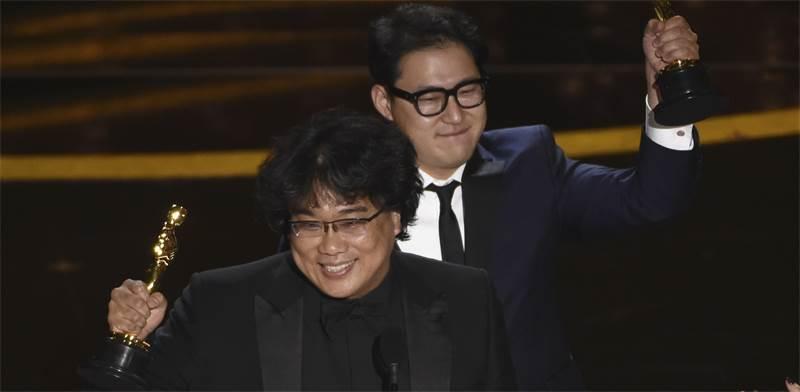 """בונג ג'ון הו והאן ג'ין וון אחרי הזכייה בפרס התסריט הטוב ביותר בטקס האוסקר עבור הסרט """"פרזיטים"""" / צילום: כריס פיזלו, AP"""