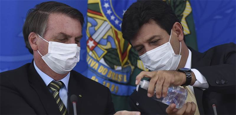מימין: שר הבריאות הברזילאי לואיז אנריקה מנדטה ונשיא ברזיל ז'איר בולסונרו  / צילום: Andre Borges , AP