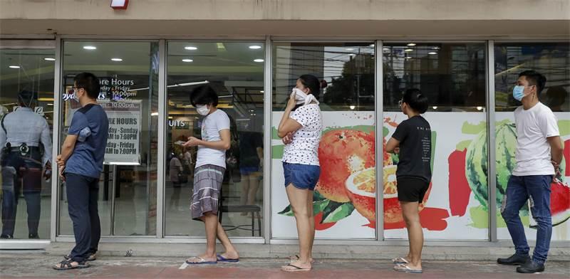 צעירים עם מסכות בתור לסופרמרקט / צילום: Aaron Favila, Associated Press