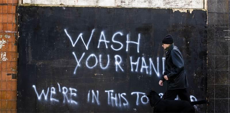 """""""שיטפו את הידיים! כולנו בזה יחד"""", גרפיטי בבריטניה / צילום: Liam McBurney / PA, Associated Press"""