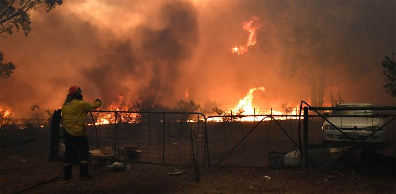 כבאי מנסה לכבות שריפה באוסטרליה / צילום: STRINGER, רויטרס
