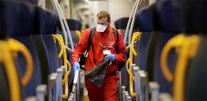 עובד מחטא רכבת באיטליה / צילום: Luca Bruno, AP