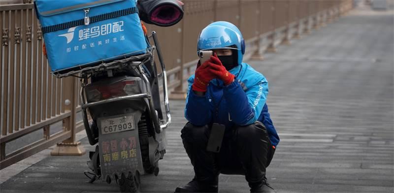 שליח אוכל בבייג'ינג השבוע / צילום: NG Han Guan, AP