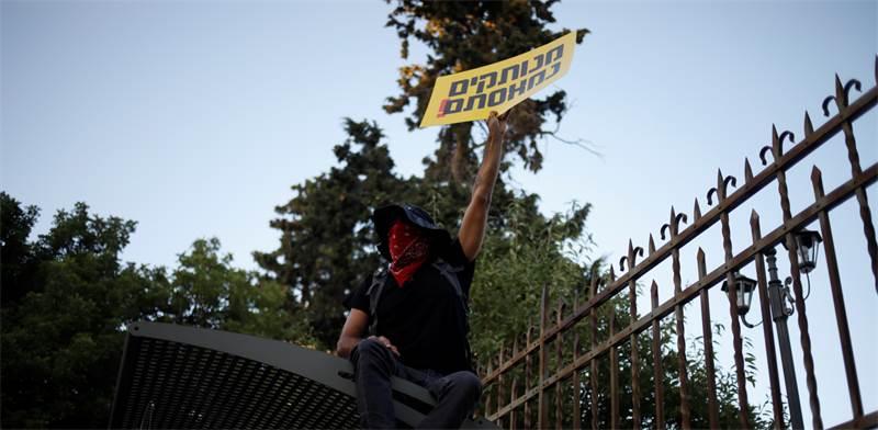 """מפגין על גדר מול מעון רה""""מ נתניהו / צילום: Ariel Schalit, Associated Press"""