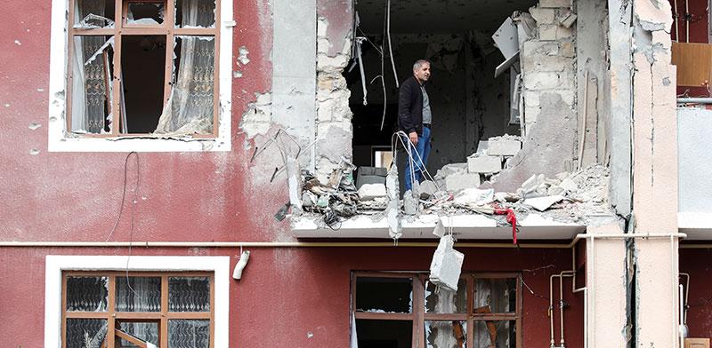 אדם ניצב השבוע על ביתו ההרוס בהפסקת האש בנגורנו־קרבך. מחיר כבד  / צילום: Umit Bektas, רויטרס