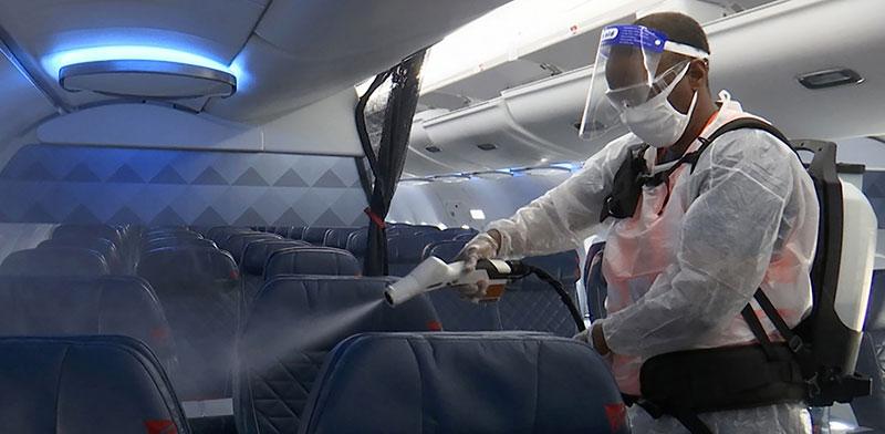 מטוס נוסעים עובר חיטוי / צילום: Nathan Ellgren, Associated Press