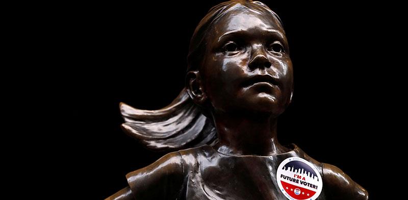"""סטיקר של הבחירות דבוק לפסל """"הילדה חסרת המורא"""" מחוץ לבורסה בניו יורק / צילום: Andrew Kelly, רויטרס"""