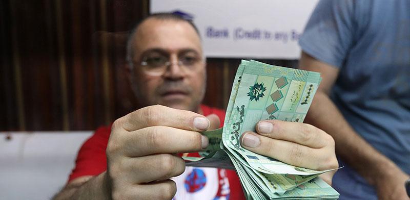 חלפן כספים בביירות  / צילום: MOHAMED AZAKIR, רויטרס