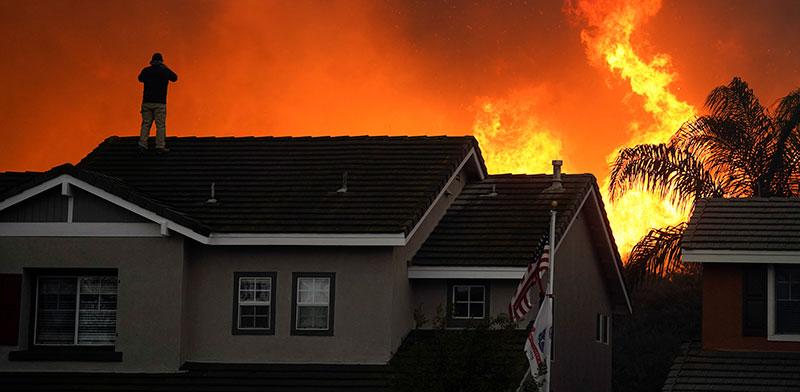 אדם על גג ביתו בקליפורניה בשבוע שעבר / צילום: Jae C. Hong, Associated Press
