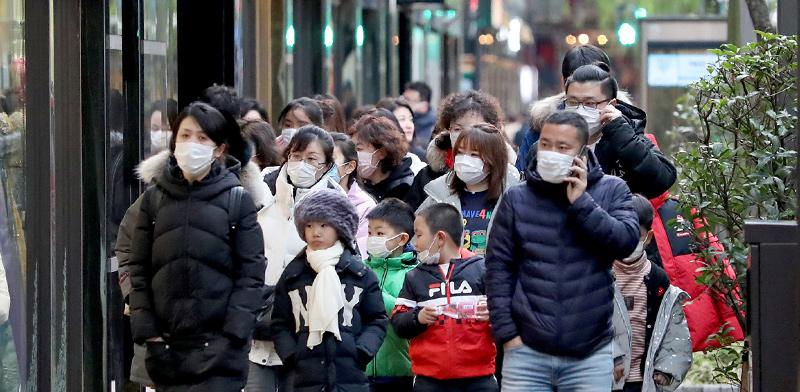 עוברי אורח חובשים מסיכות ברחוב מחשש להידבקות מנגיף הקורונה שפרץ בווהן שבסין / צילום: רויטרס