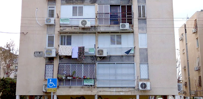 """שלטים """"חתמנו"""" תלויים על חלונות של אחד הבניינים בשכונת יפו ד' / צילום: גיא נרדי"""
