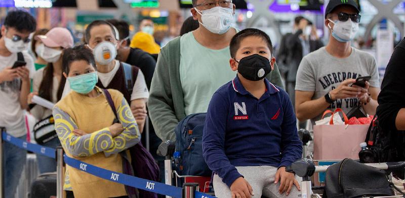 """מחכים ביציאה משדה התעופה בסין. הגלובליזציה לא """"מתה"""" / צילום: GEMUNU AMARASINGHE, AP"""