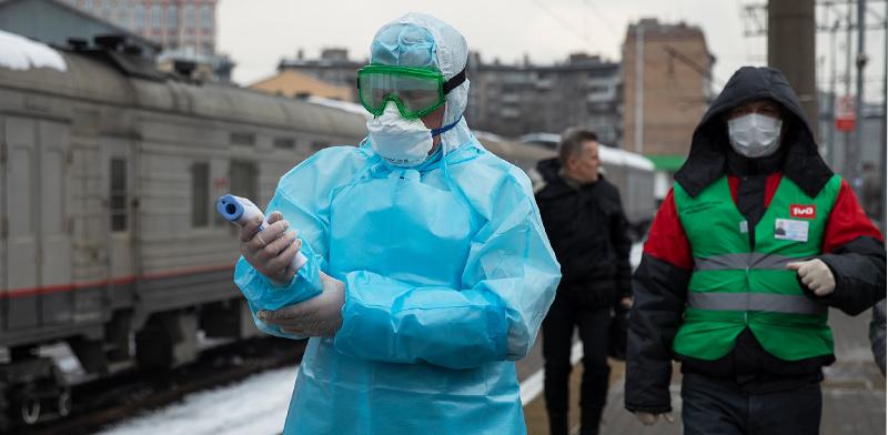 מאבטחים בשדה התעופה במוסקבה מקבלים את בואם של הנוחתים מבייג'ינג עם חליפות מגן בדרך לבדוק טמפרטורות גוף תקינות / צילום: Mark Schiefelbein, Associated Press