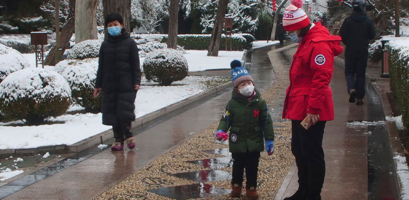 אם ובנה מטיילים בפארק הציבורי בבייג'ינג עם מסיכות הגייניות / צילום: Miriam Saleh, Associated Press