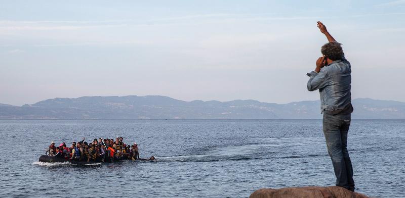 פליטים מגיעים לאי היווני לסבוס מטורקיה שנמצאת ברקע התמונה / צילום: Petros Giannakouris, Associated Press
