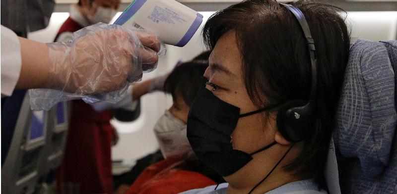 מדידת חום לנוסעת על טיסה יוצאת מסין / צילום: Associated Press