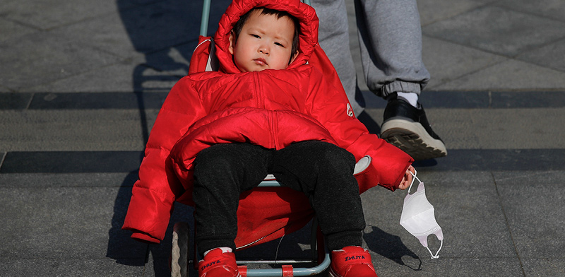 פעוט בבייג'ין מחזיק בידו במסכת המגן שלו בתחילת מגפת הקורונה / צילום: Andy Wong, Associated Press