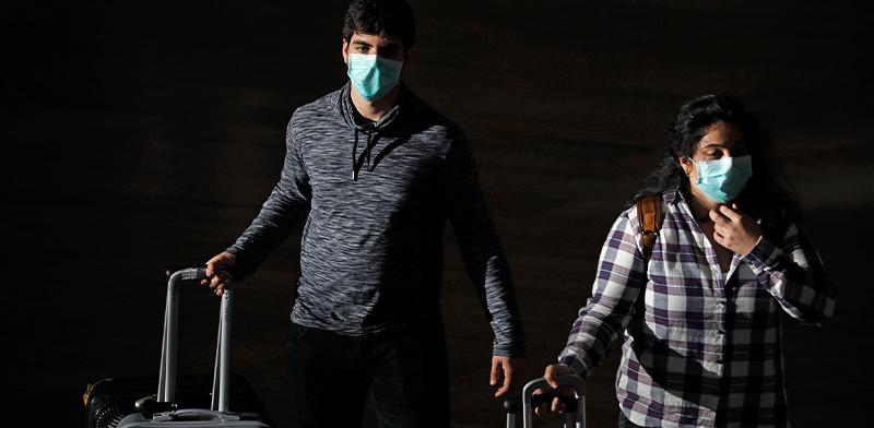 """ישראלים שחזרו מחו""""ל בלילה בנתב""""ג. משרד הבריאות הודיע שאזרחים החוזרים מכל יעד לארץ, ייכנסו לבידוד / צילום: Ariel Schalit, Associated Press"""